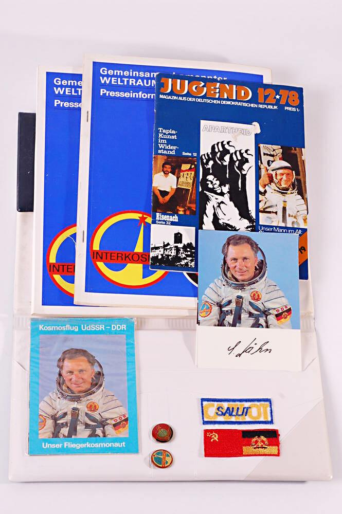 Inhalt der Interkosmos-Pressemappe mit Broschüren, Autogrammkarte, Anstecker und Aufbügler