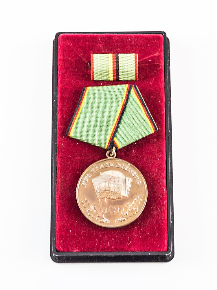 Bronze medal »For loyal service KVP« in a casket with wine-red fabric