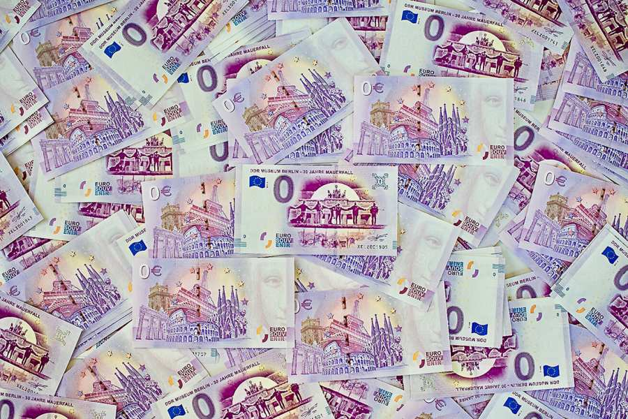 zero euro banknote in a pile of many banknotes
