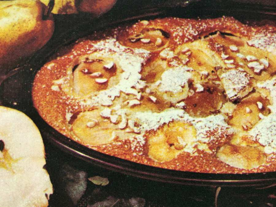 Pear Casserole dusted with icing sugar and fresh pears next to the baking form